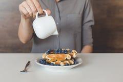 倾倒在鲜美奶蛋烘饼之上的妇女甜糖浆 图库摄影