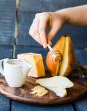 倾倒蜂蜜新鲜的梨切片和乳酪在一个木板之上 免版税库存图片