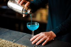 倾吐一个新鲜和甜蓝色鸡尾酒的男服务员入玻璃 免版税库存照片