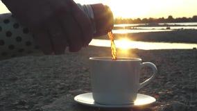 倾吐一个杯子从热水瓶的精神充沛的芬芳饮料在与美好的光芒的日落从太阳 特写镜头 股票视频