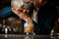 倾吐一个酒精鸡尾酒的侍酒者入与一个大冰块的一块玻璃 免版税库存图片