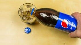 倾吐一杯从瓶的百事可乐 免版税库存图片