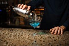倾吐与蓝色酒的男服务员手新饮料从振动器入玻璃使用过滤器 免版税库存图片