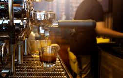 倾吐从咖啡机的热奶咖啡咖啡,关闭射击 免版税库存照片