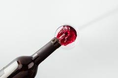 倾吐从在白色隔绝的玻璃的瓶的红葡萄酒 免版税库存图片