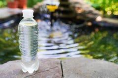 倾吐从在被弄脏的绿色自然背景的瓶的饮用水 免版税库存照片