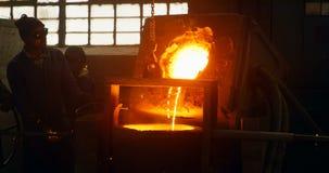 倾吐从容器的工作者熔融金属在铸造厂车间4k 影视素材