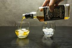 倾吐从瓶的威士忌酒入一杯冰 免版税库存照片