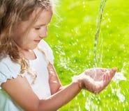 倾吐入孩子的手的净水小河 免版税库存照片