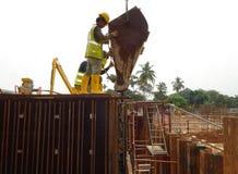 倾吐具体泥浆的建筑工人入增强混凝土墙模板 免版税库存照片