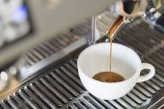 倾吐到从咖啡机器, selec的白色杯子的特写镜头浓咖啡 免版税库存照片
