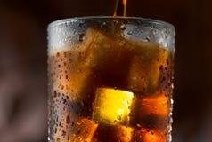 倾吐在与冰块的玻璃的可乐 免版税库存图片
