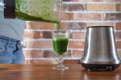 倾吐在从搅拌器的玻璃绿色圆滑的人的妇女 免版税库存图片