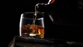 倾吐在从瓶的玻璃的威士忌酒 冰块 影视素材
