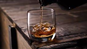 倾吐在从瓶的玻璃的威士忌酒 冰块 股票录像