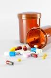 倾吐在棕色瓶外面的药片 库存照片