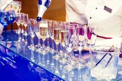 倾吐在玻璃的侍者个人服务的香宾在明亮的蓝色立场 在事件的承办酒席服务,合作会议,党, w 免版税库存照片
