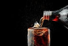 倾吐在玻璃的汽水与在黑暗的背景的冰飞溅 库存照片