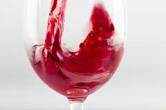 倾吐在玻璃的红葡萄酒隔绝在白色 库存图片