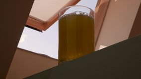 倾吐在玻璃的黄色柠檬水 t 开窗口在背景的顶楼 股票录像