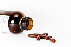 倾吐在白色背景的棕色瓶外面的布朗药片 免版税库存图片