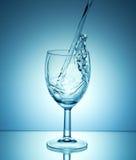 倾吐在蓝色背景的白葡萄酒 免版税库存图片