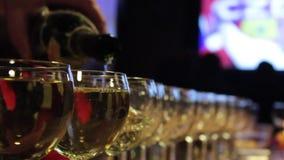 倾吐在许多玻璃的白葡萄酒。 股票录像
