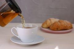 倾吐在轻的背景的杯子的茶 茶壶和早餐概念 免版税库存图片