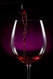 倾吐在黑色的红葡萄酒 库存照片