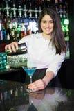 倾吐在玻璃的俏丽的侍酒者一份蓝色马蒂尼鸡尾酒饮料 库存图片