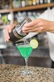 倾吐在玻璃的英俊的男服务员一个鸡尾酒 免版税图库摄影