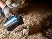 倾吐水入有一个老咖啡罐的一个烧杯 免版税图库摄影