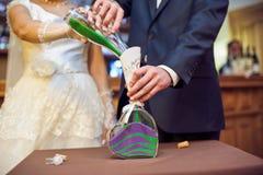倾吐沙子的手在沙子仪式期间 免版税库存照片