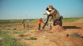 倾吐混凝土的建筑工人对在地面的一个孔从混凝土搅拌机卡车在建造场所 股票录像
