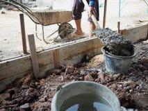 倾吐混杂的混凝土的工作者在建造场所用桶提 库存照片
