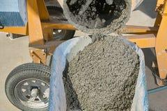 倾吐湿水泥的搅拌器入独轮车关闭  库存照片