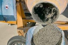 倾吐湿水泥的混凝土搅拌机入独轮车 图库摄影