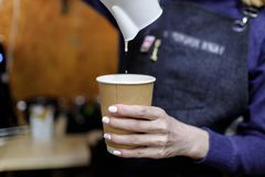 倾吐热奶咖啡玻璃的年轻barista女孩 库存图片