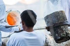 倾吐熔融金属的工作者对熔铸菩萨雕象 免版税库存图片