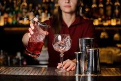 倾吐甜红色酒精饮料的女性男服务员入玻璃 库存图片