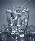 倾吐的冰块到饮料杯水里 飞溅水 库存照片