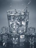 倾吐的冰块到饮料杯水里 飞溅水 免版税库存照片