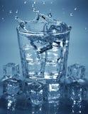 倾吐的冰块到饮料杯水里 库存照片