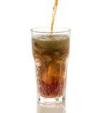 倾吐的可乐到与被隔绝的冰块的玻璃里 免版税库存图片
