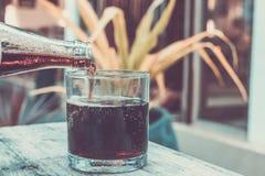 倾吐的可乐从瓶到在热带背景的玻璃 库存照片