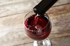 倾吐的可口红葡萄酒到玻璃里 库存图片