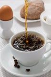 倾吐的咖啡到杯子里 免版税库存图片