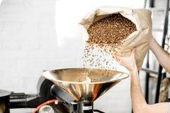 倾吐的咖啡到烘烤器机器里 库存照片