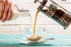 倾吐的咖啡和牛奶到杯子里 免版税库存照片