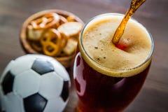 倾吐的啤酒到与快餐和橄榄球的玻璃里 库存照片